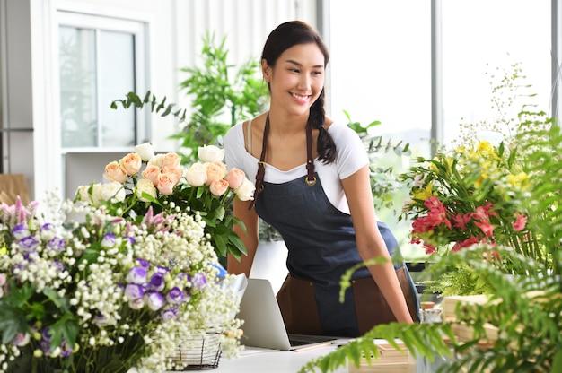 Joven empresaria asiática / dueña de una tienda / florista de una pequeña tienda de flores