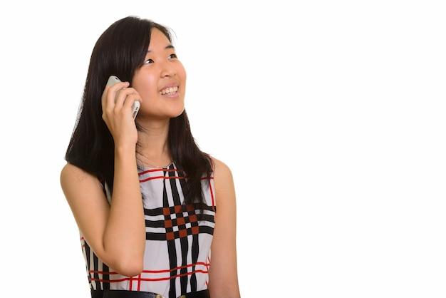 Joven empresaria asiática feliz hablando por teléfono móvil aislado