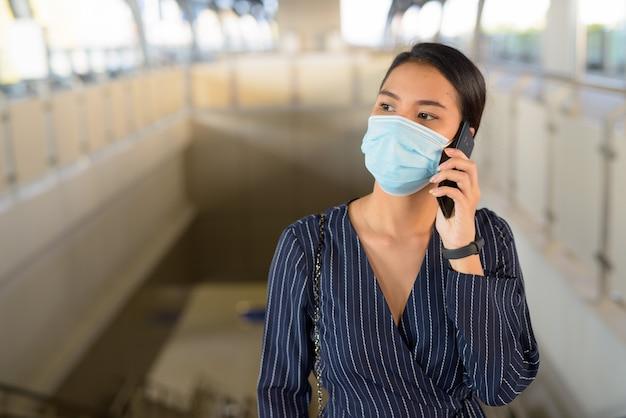 Joven empresaria asiática con máscara pensando y hablando por teléfono en la estación de skytrain