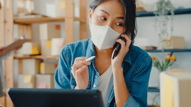 Joven empresaria asiática con mascarilla usando teléfono móvil recibiendo orden de compra y comprobando el producto en el trabajo de stock en la oficina en casa