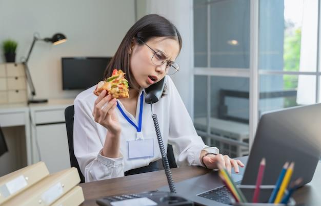 Joven empresaria asiática con pizza snack mientras habla por teléfono con los clientes debido a trabajar hasta tarde.