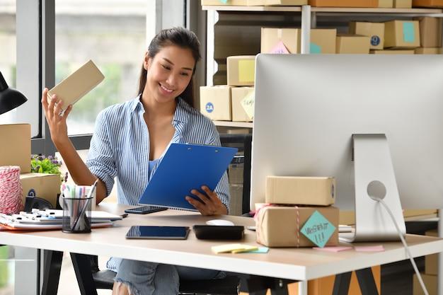 Joven empresaria asiática propietaria de negocio que trabaja con la computadora en casa