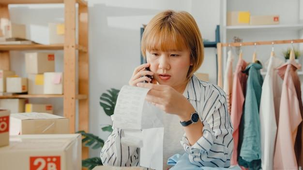 Joven empresaria asiática que usa un teléfono inteligente que recibe la orden de compra y verifica el producto en el trabajo de stock en la oficina en casa