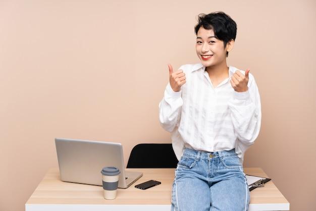 Joven empresaria asiática en su lugar de trabajo dando un gesto de aprobación