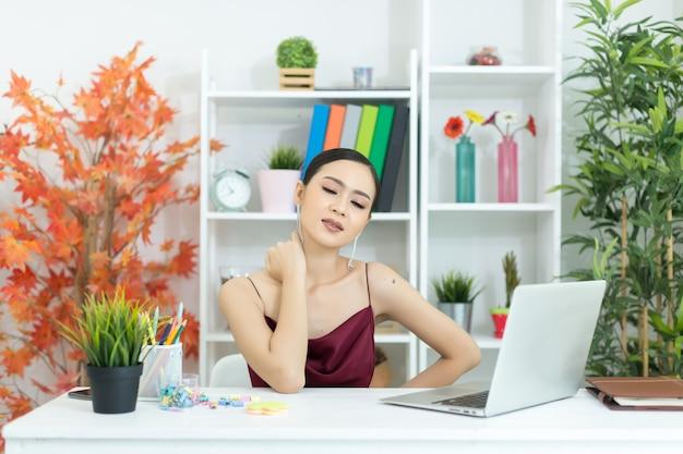 Joven empresaria asiática tocando masaje cuello rígido