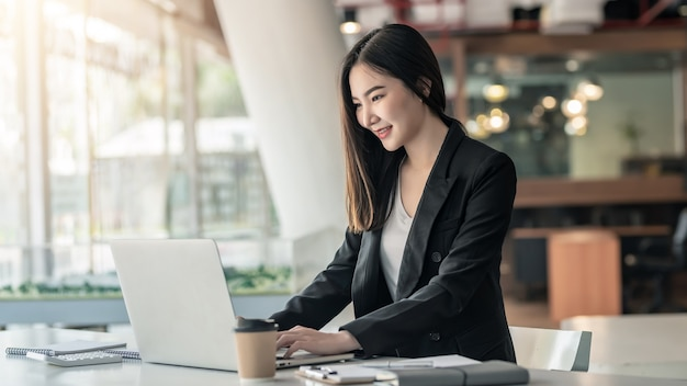 Joven empresaria asiática trabajando en una computadora portátil en una oficina moderna.
