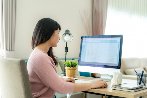 Joven empresaria asiática usando computadora revisando el trabajo de correo electrónico desde casa