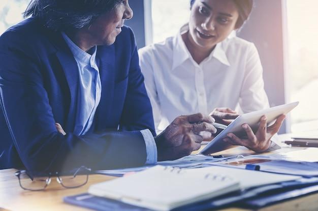 Joven empresaria atractiva que trabaja con touchpad ha sido guiada y consultada por un colega senior