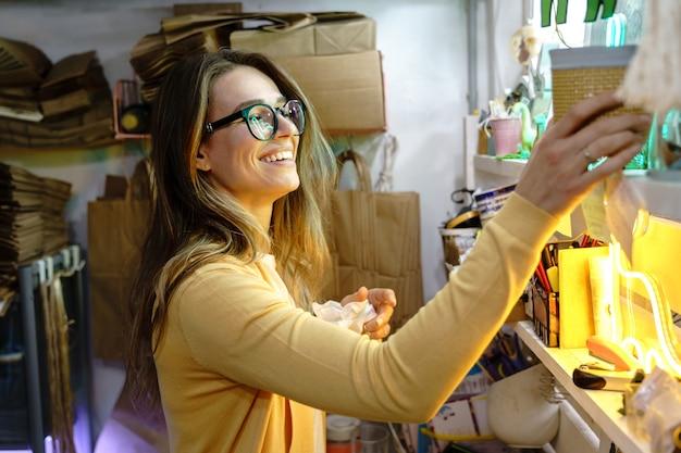 Joven empresaria autónoma elige el paquete para la entrega del pedido del cliente desde la tienda de comercio electrónico