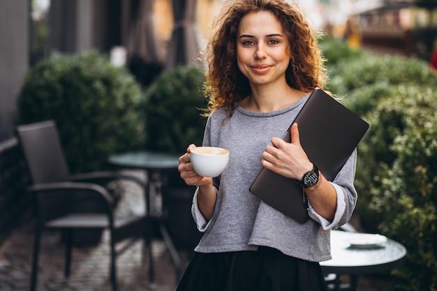 Joven empresaria bebiendo café fuera de café con laptop
