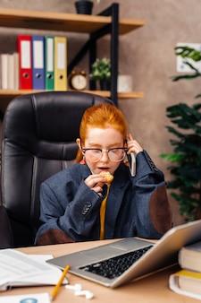 Joven empresaria. bonita chica positiva comiendo una galleta mientras realiza una llamada telefónica