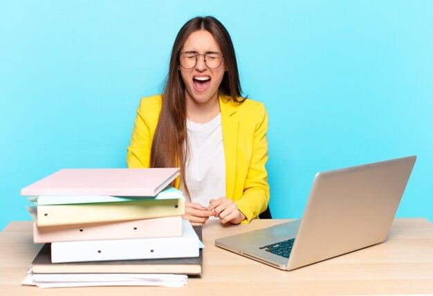 Joven empresaria bonita gritando agresivamente, luciendo muy enojada, frustrada, indignada o molesta, gritando no