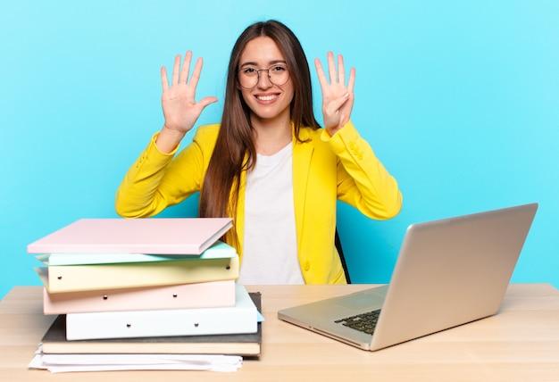 Joven empresaria bonita sonriendo y mirando amistosamente, mostrando el número nueve o noveno con la mano hacia adelante, contando hacia atrás
