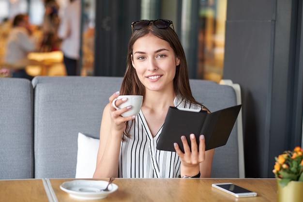 Joven empresaria en un café leyendo un libro electrónico y tomando café