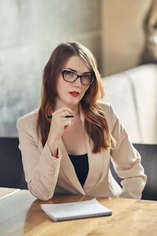 Joven empresaria caucásica con el cuaderno. mujer con gafas en un café