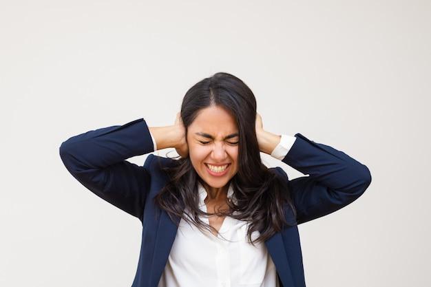 Joven empresaria cerrando los oídos