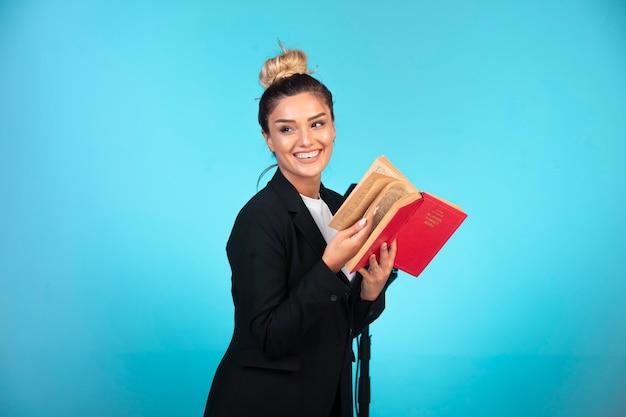 Joven empresaria en chaqueta negra sosteniendo un libro de tareas y se siente positiva.
