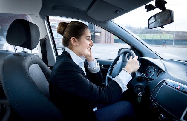 Joven empresaria conduciendo un coche y hablando por teléfono