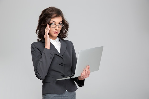 Joven empresaria confiada bastante concentrada sosteniendo el portátil y tocando sus gafas