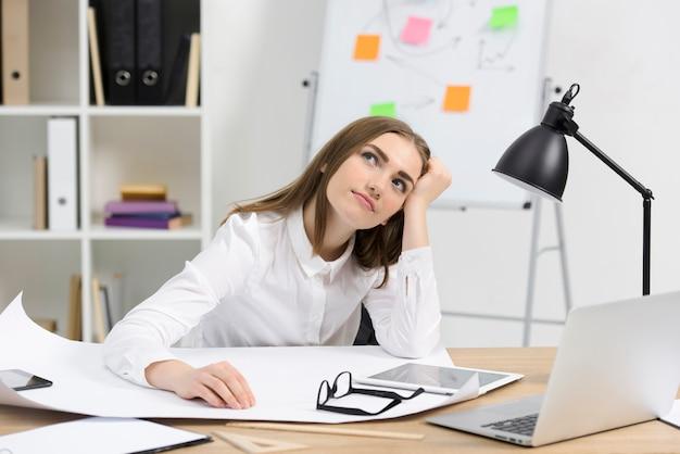 Joven empresaria contemplada con papel blanco; anteojos y tableta digital en escritorio de madera.