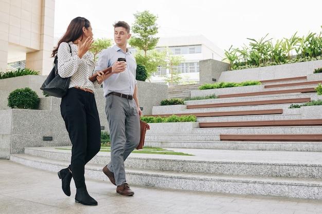 Joven empresaria emocional activamente gesticulando y hablando con su colega cuando están caminando en la calle