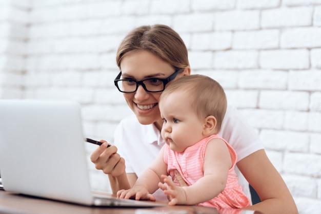 Joven empresaria entretiene lindo bebé.