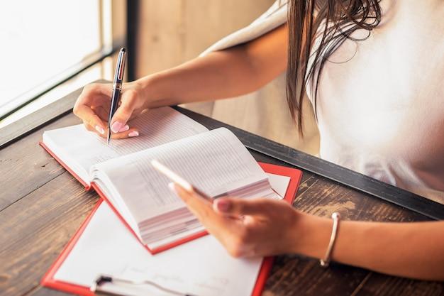 Joven empresaria está escribiendo planes en el cuaderno mientras sostiene el teléfono inteligente en el café.