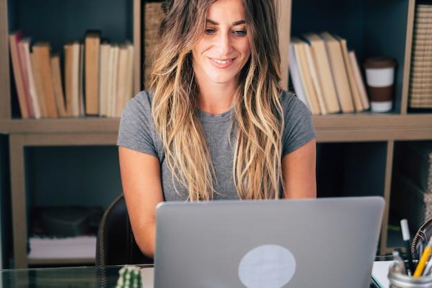 Joven empresaria escribir en la computadora portátil en casa en la actividad de trabajo de trabajo de oficina de trabajo inteligente