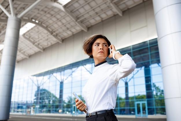 Joven empresaria exitosa hablando por teléfono, de pie cerca del centro de negocios.