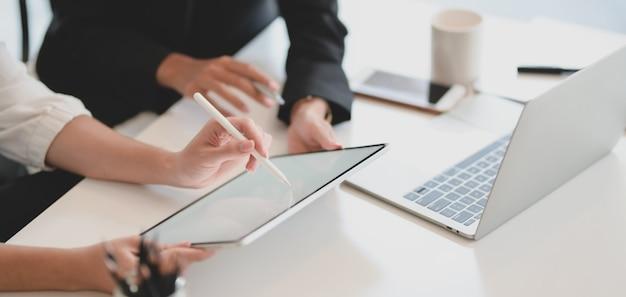 Joven empresaria explicando su idea a su compañero de trabajo con tableta de pantalla en blanco