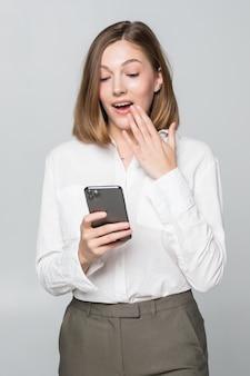 Joven empresaria con expresión de la cara de sorpresa está utilizando un teléfono inteligente en la pared blanca