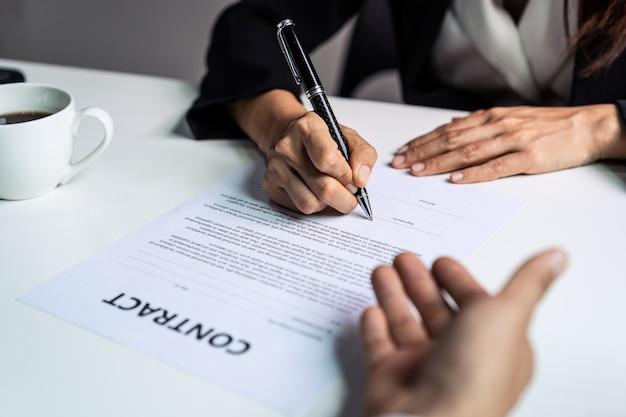 Joven empresaria firmando contrato, acuerdo exitoso de asociación después de la reunión
