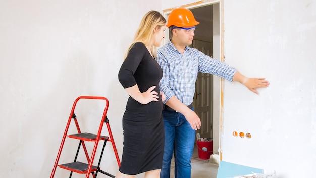 Joven empresaria hablando con la construcción de la casa contratista masculino en construcción.