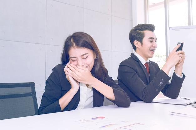 Joven empresaria está hablando en secreto por teléfono en el trabajo