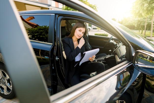 Joven empresaria hablando por teléfono en el asiento del pasajero del automóvil y sosteniendo en la mano un portapapeles con papel para escribir notas