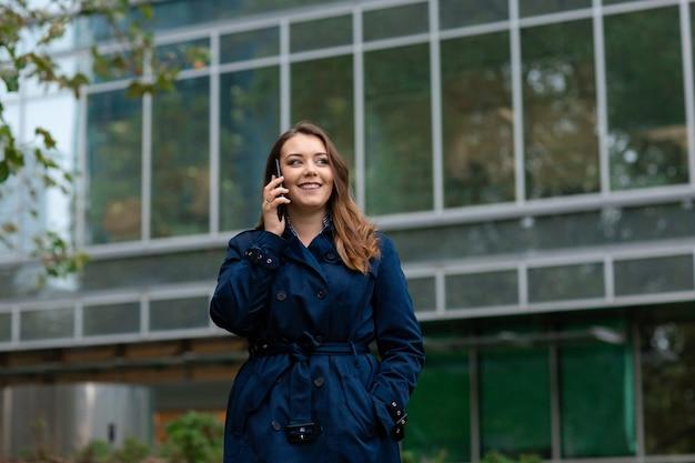 Joven empresaria hablando por teléfono móvil durante un descanso para tomar café al aire libre, cerca del edificio de oficinas