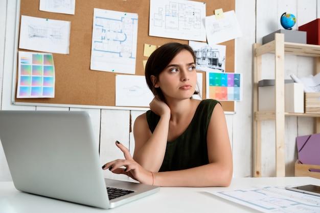 Joven empresaria hermosa pensando, sentado en el lugar de trabajo con ordenador portátil