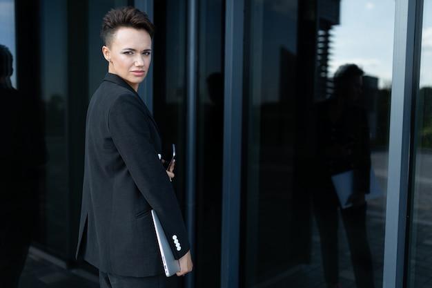 Joven empresaria hermosa posando contra el edificio moderno