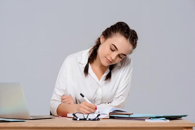 Joven empresaria hermosa sentada en el lugar de trabajo, escribiendo sobre la pared púrpura