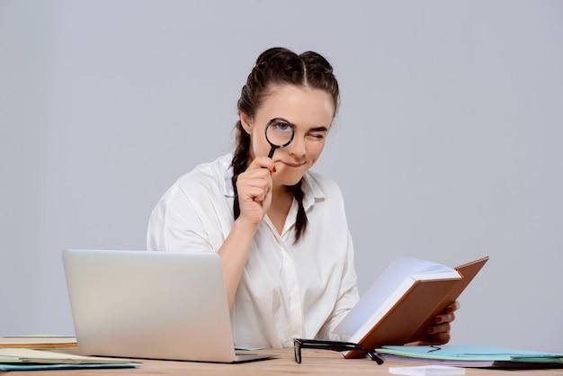 Joven empresaria hermosa sentada en el lugar de trabajo, con libro y lupa