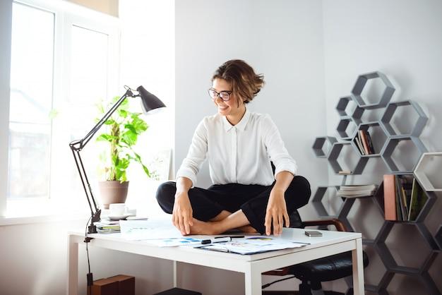 Joven empresaria hermosa sentada en la mesa en el lugar de trabajo en la oficina.