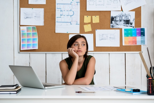 Joven empresaria hermosa soñando, sentado en el lugar de trabajo con ordenador portátil