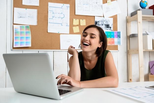 Joven empresaria hermosa sonriendo, sentado en el lugar de trabajo escribiendo en la computadora portátil