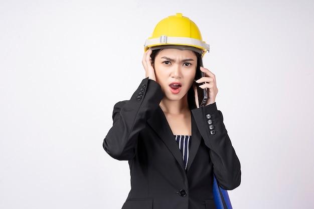Joven empresaria infeliz mientras habla por móvil en blanco