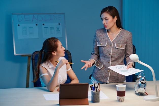 Joven empresaria irritada hablando con el diseñador de ui y regañándola por trabajar lento la noche antes de la fecha límite