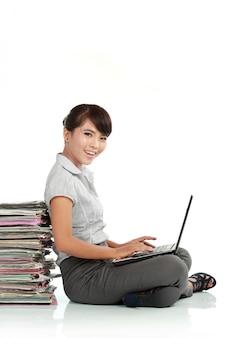 Joven empresaria con laptop y papeles
