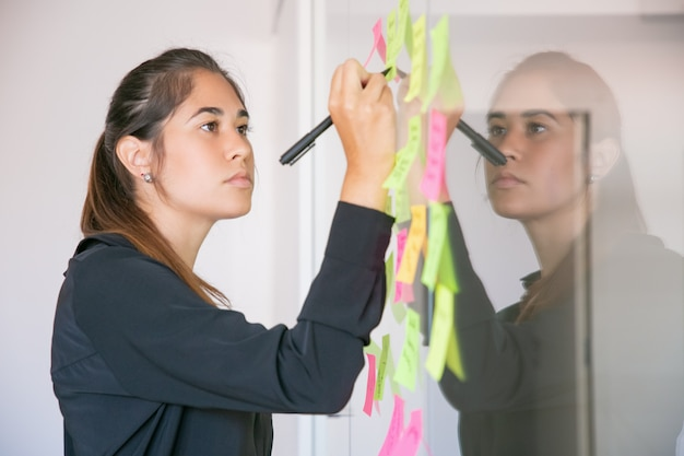 Joven empresaria latina escribiendo en etiqueta con marcador. centrado confiado hermosa morena mujer gerente compartiendo idea para proyecto y tomando nota. concepto de lluvia de ideas, negocios y formación