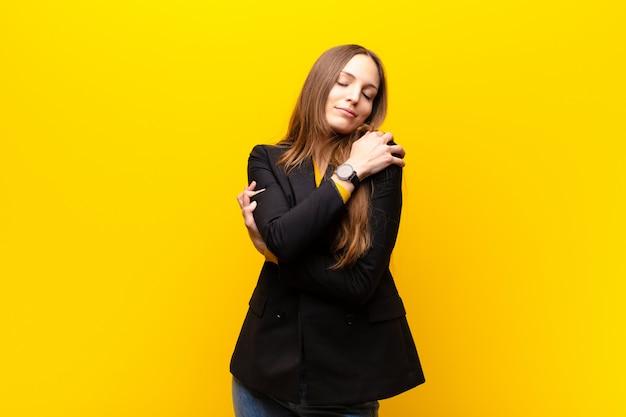 Joven empresaria linda sintiéndose enamorada, sonriendo, abrazándose y abrazándose, manteniéndose soltera, siendo egoísta y egocéntrica contra la pared naranja