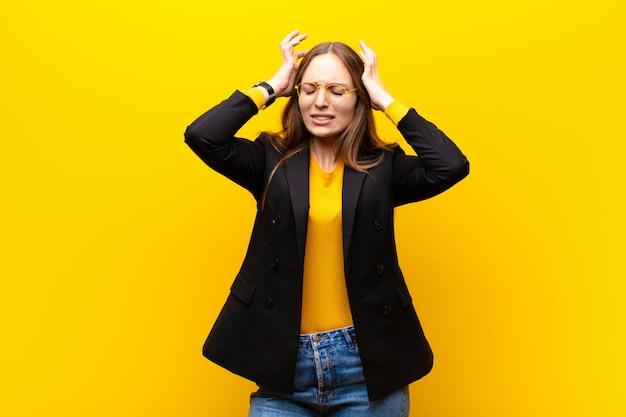 Joven empresaria linda sintiéndose estresada y frustrada, levantando las manos a la cabeza, sintiéndose cansada, infeliz y con migraña contra la pared naranja