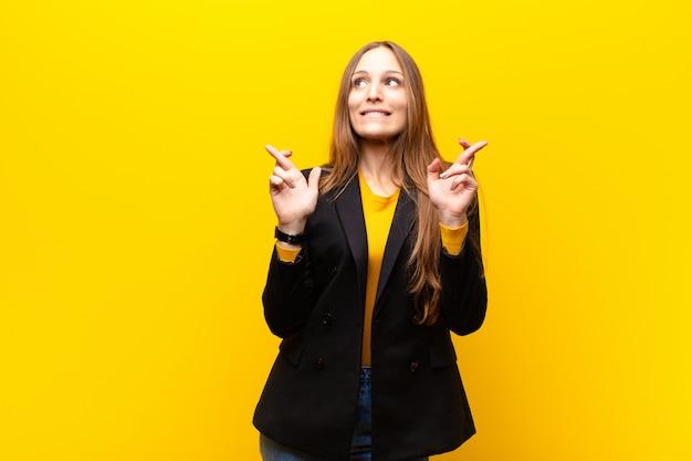 Joven empresaria linda sonriendo y cruzando ansiosamente ambos dedos, sintiéndose preocupada y deseando o esperando buena suerte contra el fondo naranja